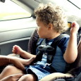 Young son into his back seat located child safety seat