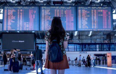 dziewczyna patrzy na rozkład lotów na lotnisku